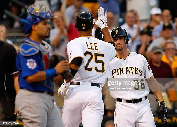 Derrek Lee of the Pittsburgh Pirates newly acquired in a trade from the Baltimore Orioles is congratulated by teammate Ryan Ludwick also just...