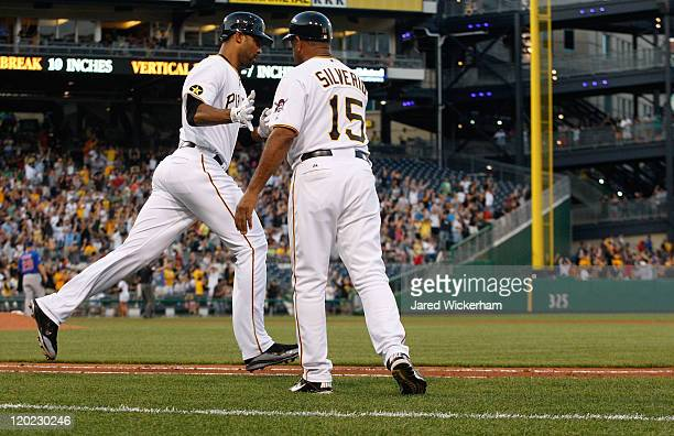 Derrek Lee of the Pittsburgh Pirates newly acquired in a trade from the Baltimore Orioles is congratulated by first base coach Luis Silverio after he...
