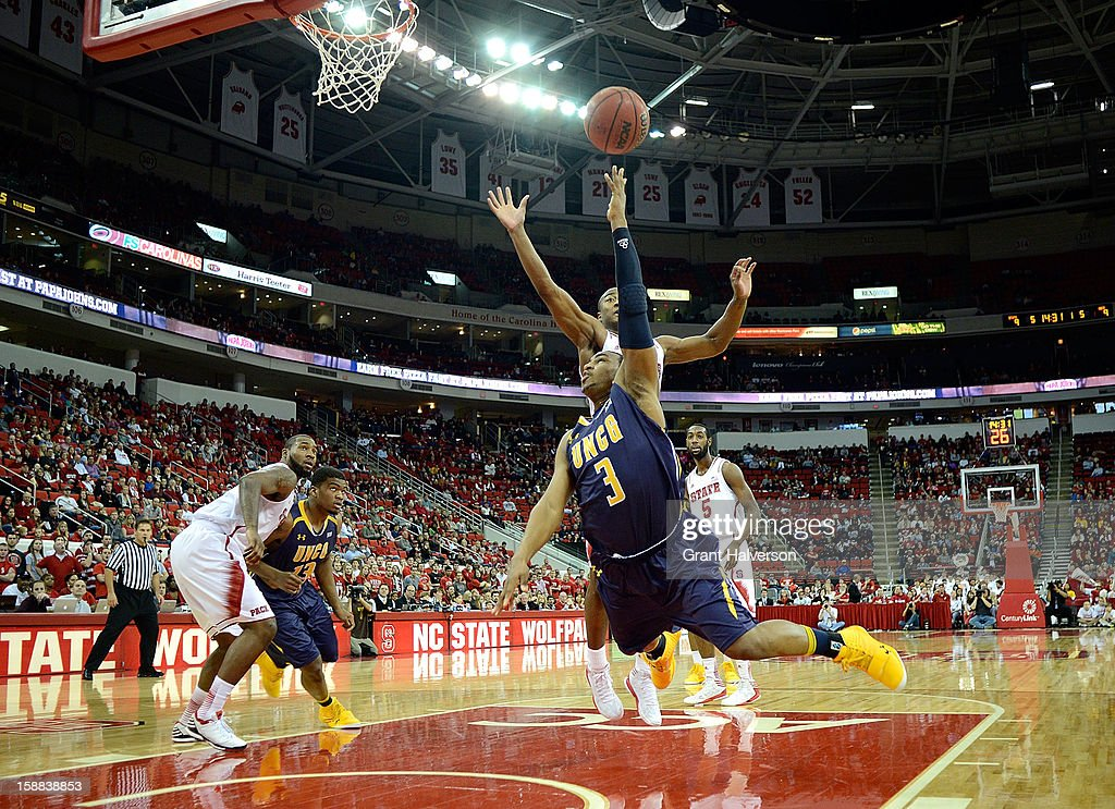 Derrell Armstrong #3 of the UNC Greensboro Spartans throws up a shot as he his fouled by Rodney Purvis #0 of the North Carolina State Wolfpack during play at PNC Arena on December 31, 2012 in Raleigh, North Carolina.