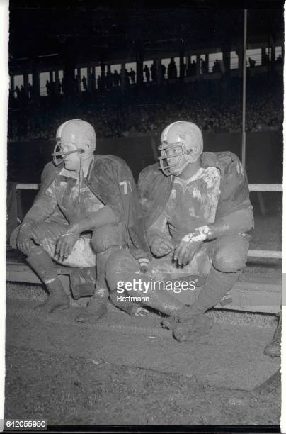 Derrell Palmer and Len Ford of the Cleveland Browns sit wet and mud splattered as they watch teammates battle the New York Giants on October 25th at...