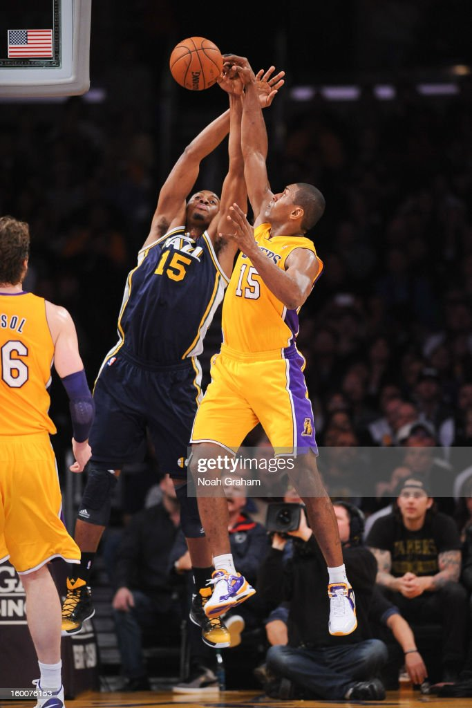 Derrick Favors #15 of the Utah Jazz and Metta World Peace #15 of the Los Angeles Lakers reach for a loose ball during their game at Staples Center on January 25, 2013 in Los Angeles, California.