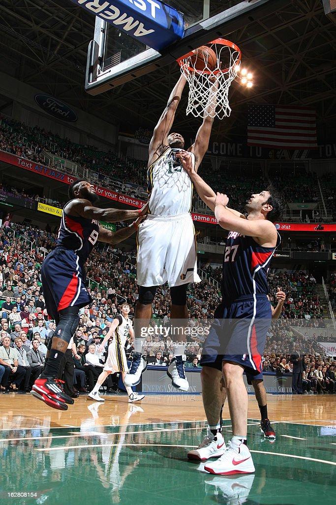 Derrick Favors #15 of the Utah Jazz dunks the ball past Zaza Pachulia #27 and Deshawn Stevenson #92 of the Atlantic Hawks at Energy Solutions Arena on February 27, 2013 in Salt Lake City, Utah.