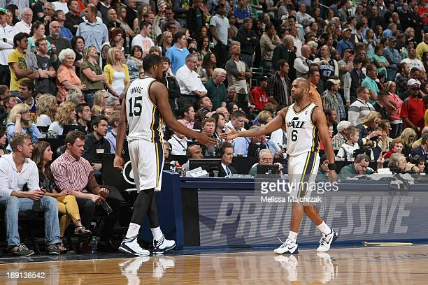 Derrick Favors of the Utah Jazz high fives teammate Jamaal Tinsley during the game against the Minnesota Timberwolves at Energy Solutions Arena on...