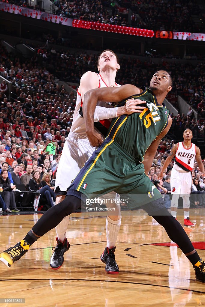 Derrick Favors #15 of the Utah Jazz is being guarded by Luke Babbitt #8 of the Portland Trail Blazers during the game between the Utah Jazz and the Portland Trail Blazers on February 2, 2013 at the Rose Garden Arena in Portland, Oregon.