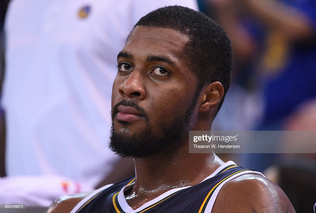 Derrick Favors of the Utah Jazz looks on from the bench against the Golden State Warriors during their NBA basketball game at ORACLE Arena on...
