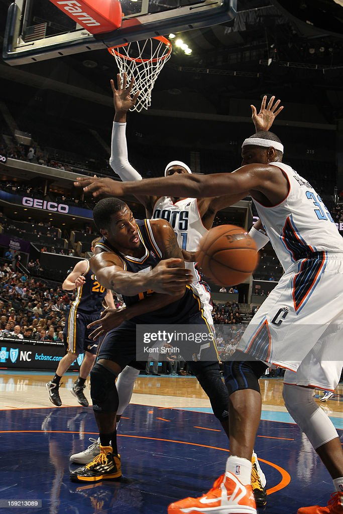 Derrick Favors #15 of the Utah Jazz passes the ball around Brendan Haywood #33 of the Charlotte Bobcats at the Time Warner Cable Arena on January 9, 2013 in Charlotte, North Carolina.