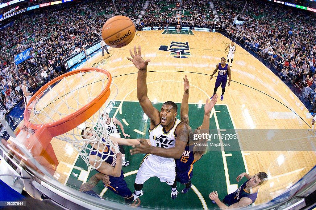 Derrick Favors of the Utah Jazz shoots past Marcus Morris of the Phoenix Suns at EnergySolutions Arena on November 01 2014 in Salt Lake City Utah...