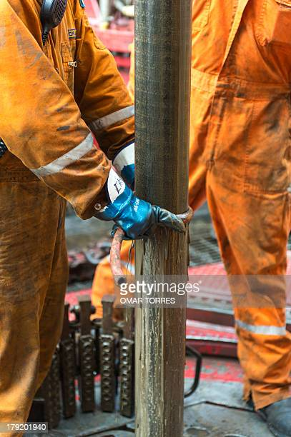 Derrick hands clean the drilling tool which has a sample of the marine seabed at La Muralla IV exploration oil rig operated by Mexican company 'Grupo...