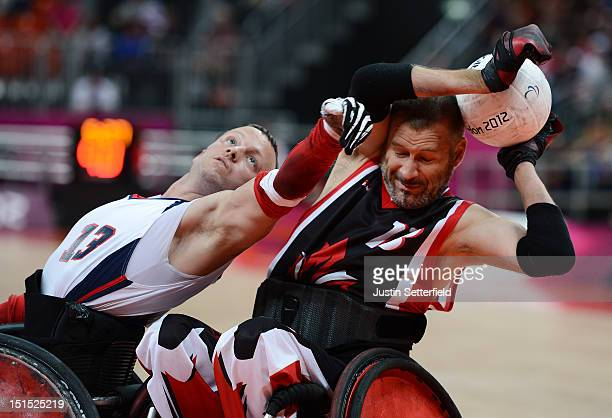Derrick Helton of the United States attempts to get the ball from Jared Funk of Canada during the Mixed Wheelchair Rugby Open semifinal match between...