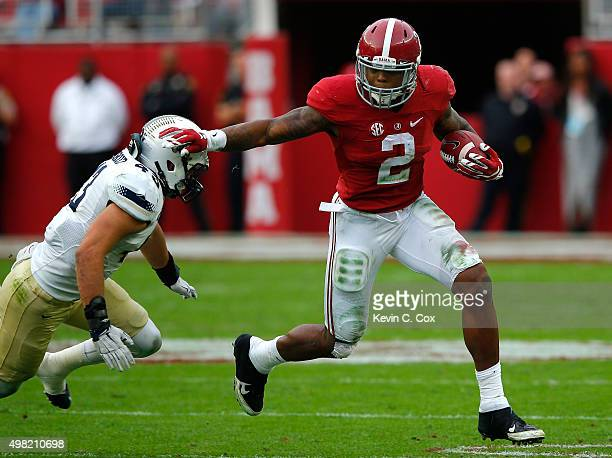 Derrick Henry of the Alabama Crimson Tide breaks a tackle by Zane Cruz of the Charleston Southern Buccaneers at BryantDenny Stadium on November 21...