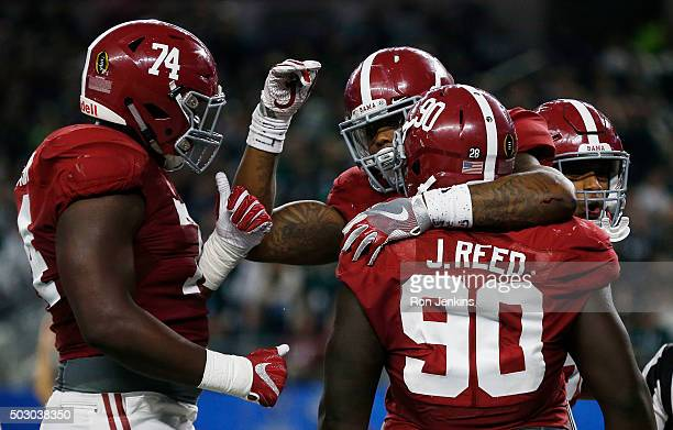 Derrick Henry of the Alabama Crimson Tide celebrates scoring a touchdown in the second quarter with teammates offensive lineman Cam Robinson and...