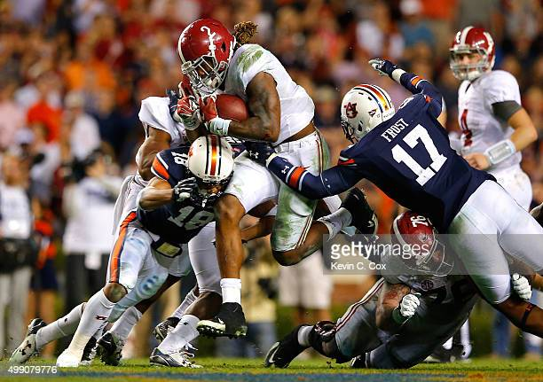 Derrick Henry of the Alabama Crimson Tide rushes against Carlton Davis and Kris Frost of the Auburn Tigers at Jordan Hare Stadium on November 28 2015...