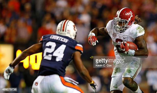 Derrick Henry of the Alabama Crimson Tide rushes against Derrick Moncrief of the Auburn Tigers at Jordan Hare Stadium on November 28 2015 in Auburn...