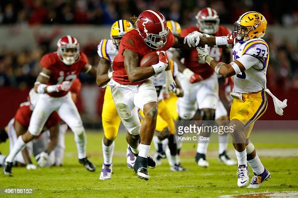 Derrick Henry of the Alabama Crimson Tide rushes away from Jamal Adams of the LSU Tigers in the second quarter at BryantDenny Stadium on November 7...