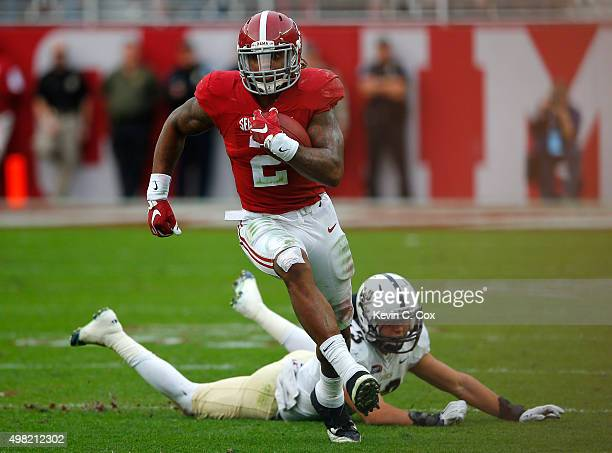 Derrick Henry of the Alabama Crimson Tide rushes past Zane Cruz of the Charleston Southern Buccaneers at BryantDenny Stadium on November 21 2015 in...
