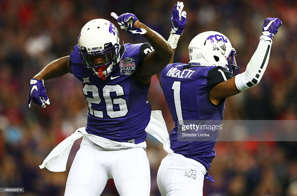 Derrick Kindred #26 celebarates with Chris Hackett #1 of the TCU Horned Frogs after a tackle in the first quarter against the Ole Miss Rebels during the Chik-fil-A Peach Bowl at Georgia Dome on December 31, 2014 in Atlanta, Georgia.