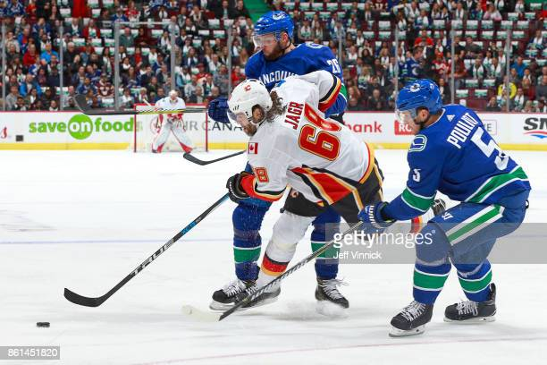 Derrick Pouliot looks on as teammate Thomas Vanek of the Vancouver Canucks checks Jaromir Jagr of the Calgary Flames during their NHL game at Rogers...