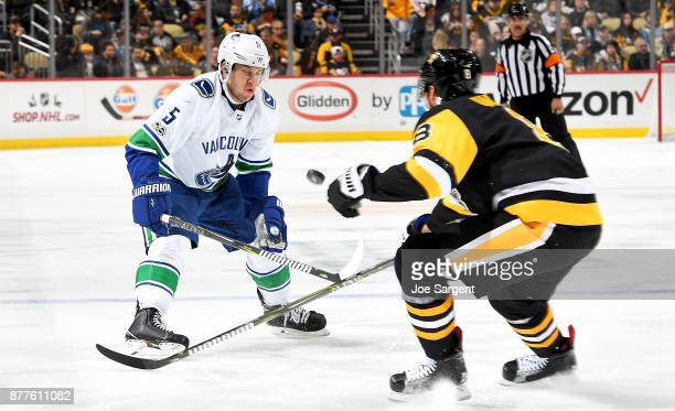 Derrick Pouliot of the Vancouver Canucks and Brian Dumoulin of the Pittsburgh Penguins battle for the puck at PPG Paints Arena on November 22 2017 in...