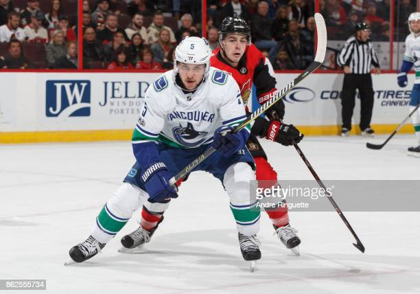 Derrick Pouliot of the Vancouver Canucks skates for the puck as JeanGabriel Pageau of the Ottawa Senators defends against at Canadian Tire Centre on...