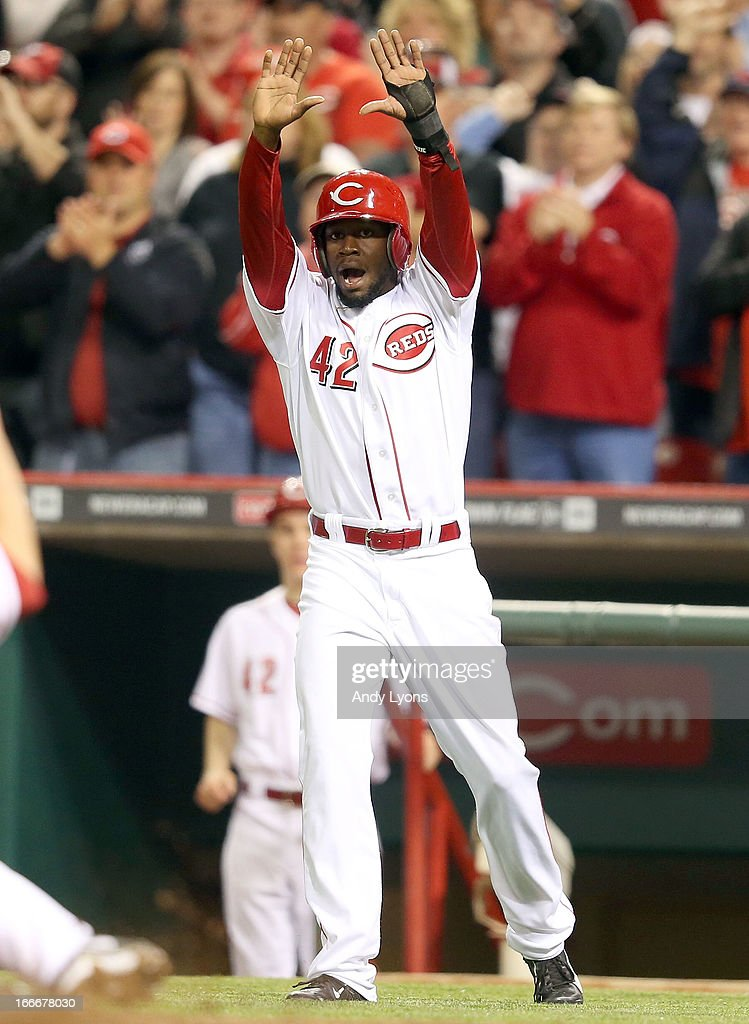 Derrick Robinson of the Cincinnati Reds celebrates as Zach Cozart scores in the 8th inning during the game against the Philadelphia Phillies at Great American Ball Park on April 15, 2013 in Cincinnati, Ohio. All uniformed team members are wearing jersey number 42 in honor of Jackie Robinson Day.