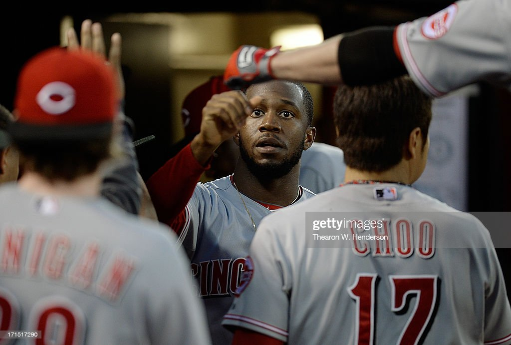 Derrick Robinson #15 (C) of the Cincinnati Reds is congratulated by teammates after he scored on a bases loaded walk to Jay Bruce #32 in the fifth inning against the Oakland Athletics at O.co Coliseum on June 25, 2013 in Oakland, California.