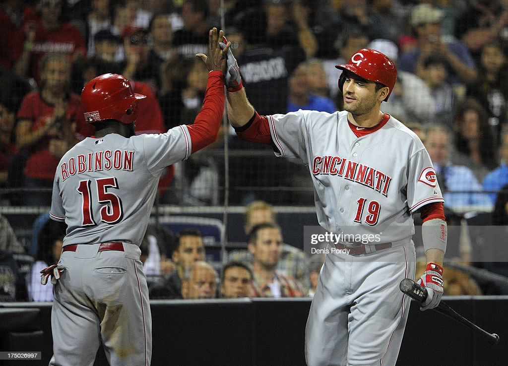 Derrick Robinson #15 of the Cincinnati Reds, left, is congratulated by <a gi-track='captionPersonalityLinkClicked' href=/galleries/search?phrase=Joey+Votto&family=editorial&specificpeople=759319 ng-click='$event.stopPropagation()'>Joey Votto</a> #19 after he scored during the fifth inning of a baseball game against the San Diego Padres at Petco Park on July 29, 2013 in San Diego, California.