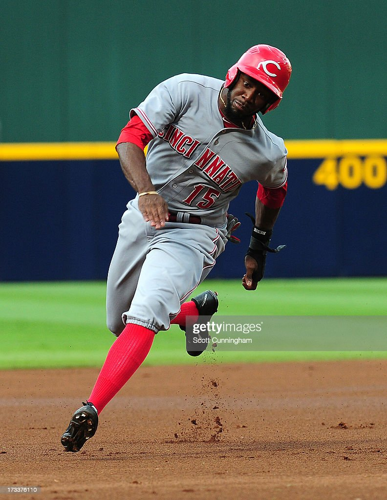 Derrick Robinson #15 of the Cincinnati Reds rounds third base to score a first inning run against the Atlanta Braves at Turner Field on July 12, 2013 in Atlanta, Georgia.