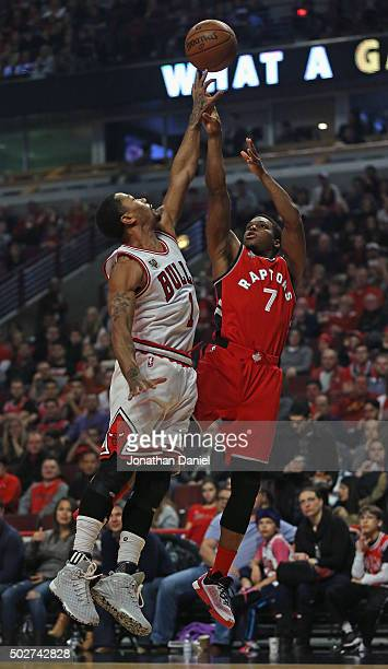 Derrick Rose of the Chicago Bulls blocks a shot by Kyle Lowry of the Toronto Raptors at the United Center on December 28 2015 in Chicago Illinois...
