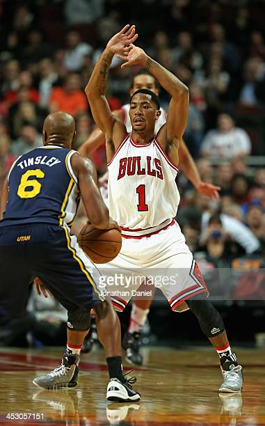 Derrick Rose of the Chicago Bulls defends against Jamaal Tinsley of the Utah Jazz at the United Center on November 8 2013 in Chicago Illinois The...