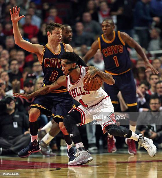 Derrick Rose of the Chicago Bulls drives against Matthew Dellavedova of the Cleveland Cavaliers during the season opening game at the United Center...