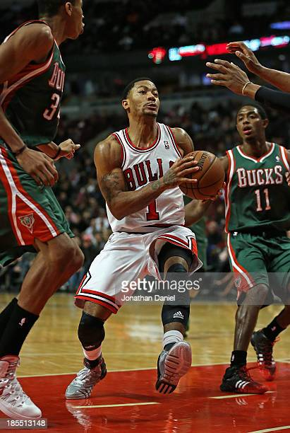 Derrick Rose of the Chicago Bulls drives between Giannis Antetokounmpo and Brandon Knight of the Milwaukee Bucks during a preseason game at the...