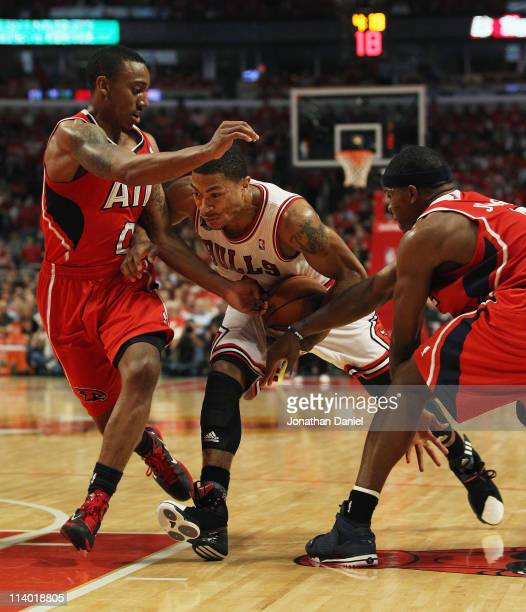 Derrick Rose of the Chicago Bulls drives between Jeff Teague and Joe Johnson of the Atlanta Hawks in Game Five of the Eastern Conference Semifinals...