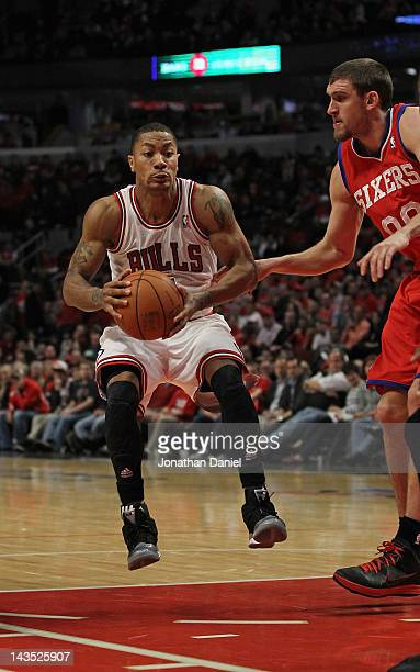 Derrick Rose of the Chicago Bulls drives past Spencer Hawes of the Philadelphia 76ers and appears to injure his knee in Game One of the Eastern...