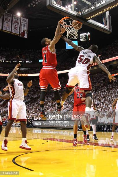 Derrick Rose of the Chicago Bulls dunks on Joel Anthony of the Miami Heat as LeBron James of the Heat looks on in the first half of Game Four of the...