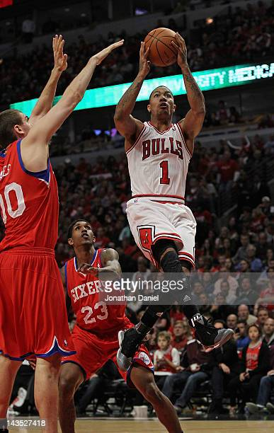 Derrick Rose of the Chicago Bulls goes up for a shot against Louis Williams and Spencer Hawes of the Philadelphia 76ers in Game One of the Eastern...