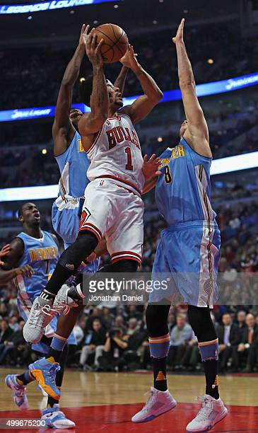 Derrick Rose of the Chicago Bulls goes up for a shot between Kenneth Faried and Danilo Gallinari of the Denver Nuggets at the United Center on...