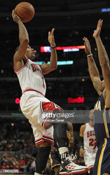Derrick Rose of the Chicago Bulls goes up for a shot in front of Dahntay Jones of the Indiana Pacers at the United Center on December 20 2011 in...