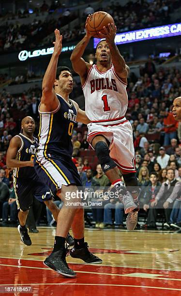 Derrick Rose of the Chicago Bulls goes up for a shot over Enes Kanter of the Utah Jazz at the United Center on November 8 2013 in Chicago Illinois...