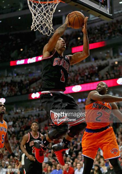 Derrick Rose of the Chicago Bulls goes up for a shot over Raymond Felton of the New York Knicks at the United Center on October 31 2013 in Chicago...