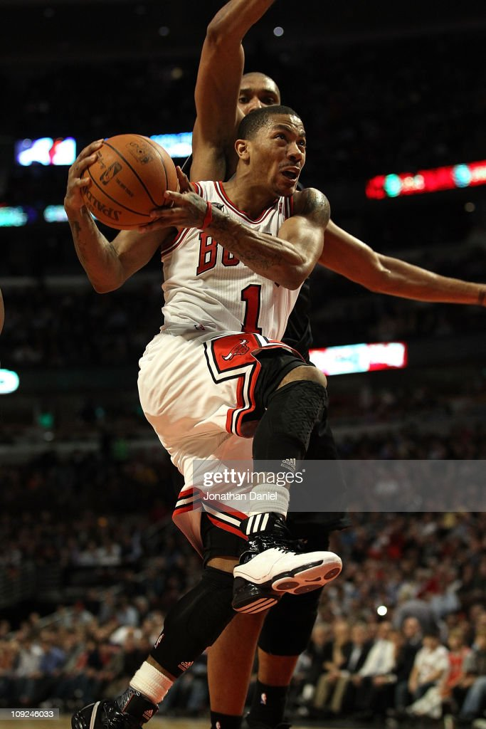 Derrick Rose #1 of the Chicago Bulls goes up for a shot past Tim Duncan #21 of the San Antonio Spurs on his way to a game and career high 42 points at the United Center on February 17, 2011 in Chicago, Illinois. The Bulls defeated the Spurs 109-99.