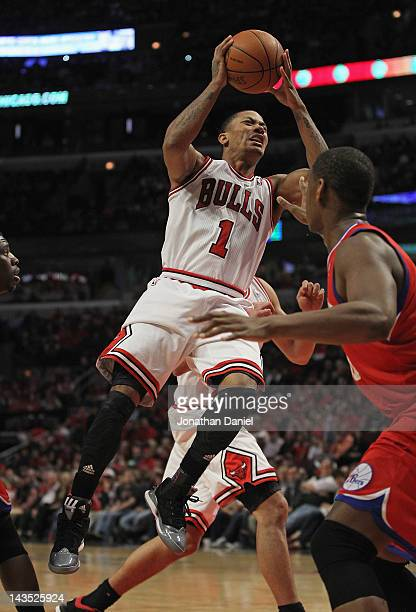 Derrick Rose of the Chicago Bulls grimaces as he goes up to pass over Lavoy Allen of the Philadelphia 76ers after apparently injuring his knee in...