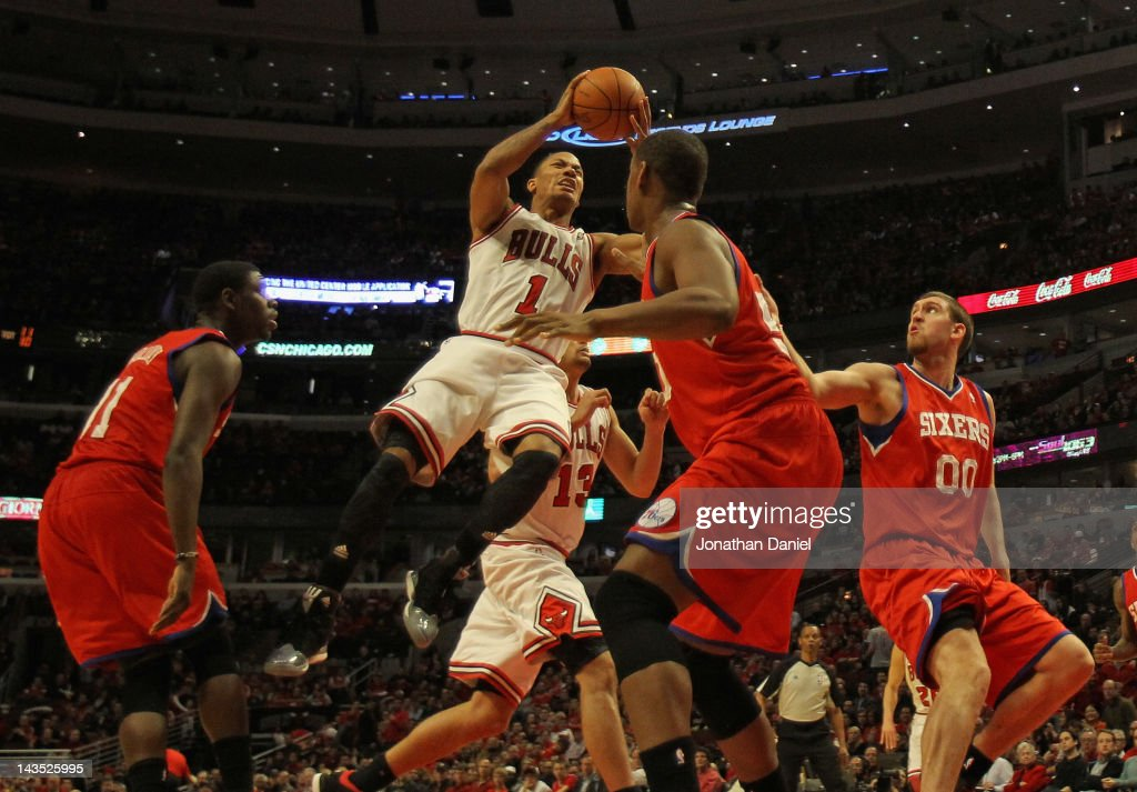 Derrick Rose of the Chicago Bulls grimaces as he goes up to pass over Lavoy Allen of the Philadelphia 76ers after apparently injuring his knee as...