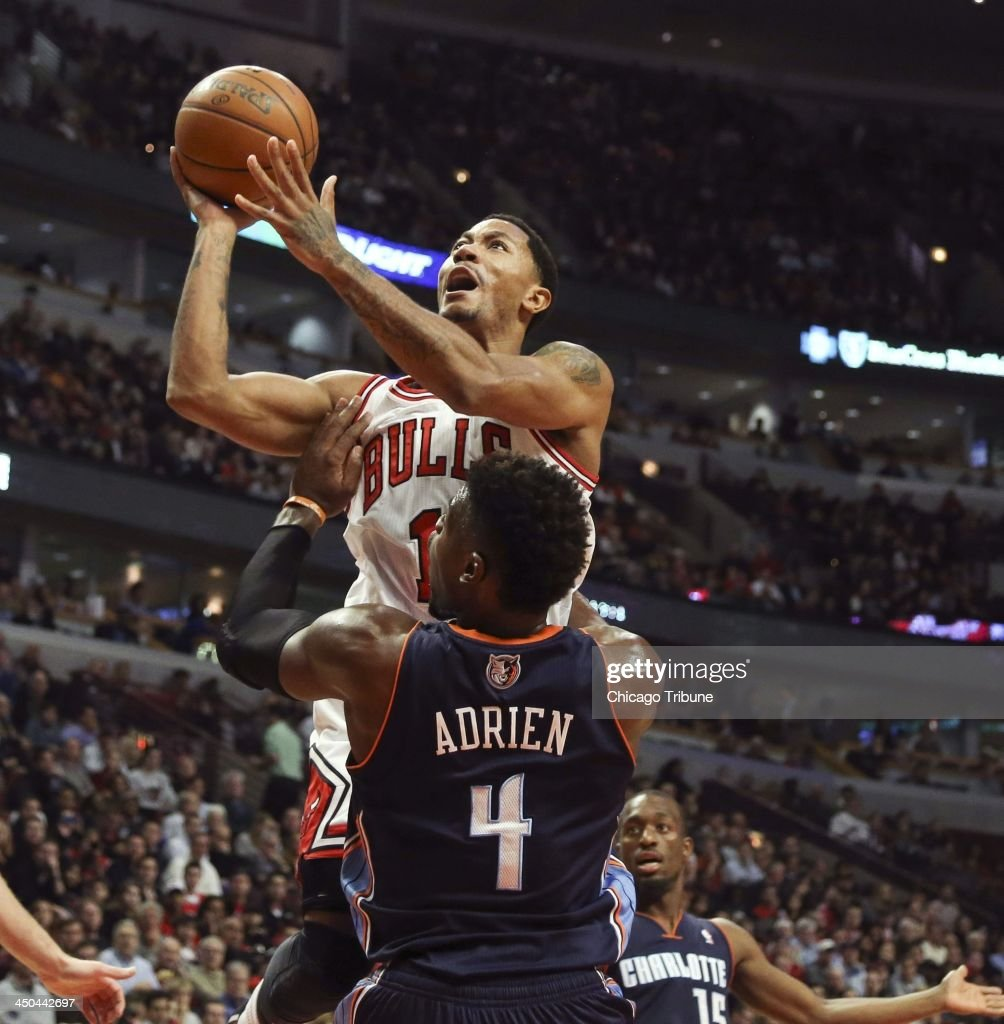 Derrick Rose (1) of the Chicago Bulls is charged with an offensive foul against Jeff Adrien (4) of the Charlotte Bobcats during the first half at the United Center in Chicago on Monday, Nov. 18, 2013.