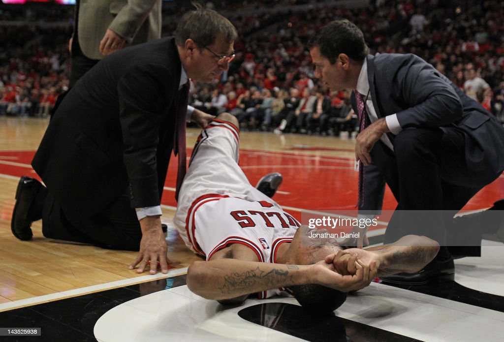 Derrick Rose #1 of the Chicago Bulls is examined after suffering an injury against the Philadelphia 76ers in Game One of the Eastern Conference Quarterfinals during the 2012 NBA Playoffs at the United Center on April 28, 2012 in Chicago, Illinois. The Bulls defeated the 76ers 103-91.