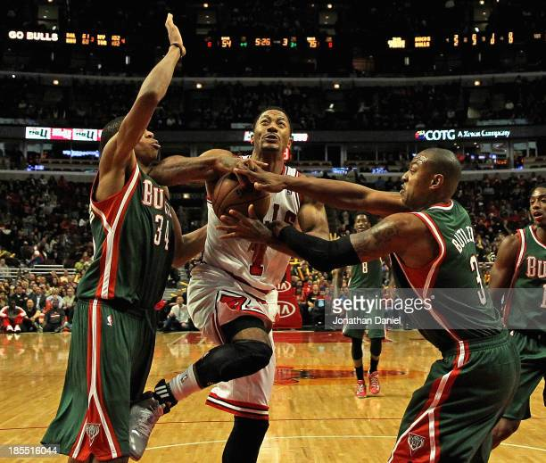 Derrick Rose of the Chicago Bulls is fouled by Caron Butler of the Milwuakee Bucks as he drives past Giannis Antetokounmpo during a preseason game at...