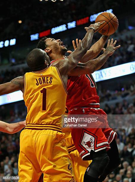 Derrick Rose of the Chicago Bulls is fouled by James Jones of the Cleveland Cavaliers at the United Center on February 12 2015 in Chicago Illinois...