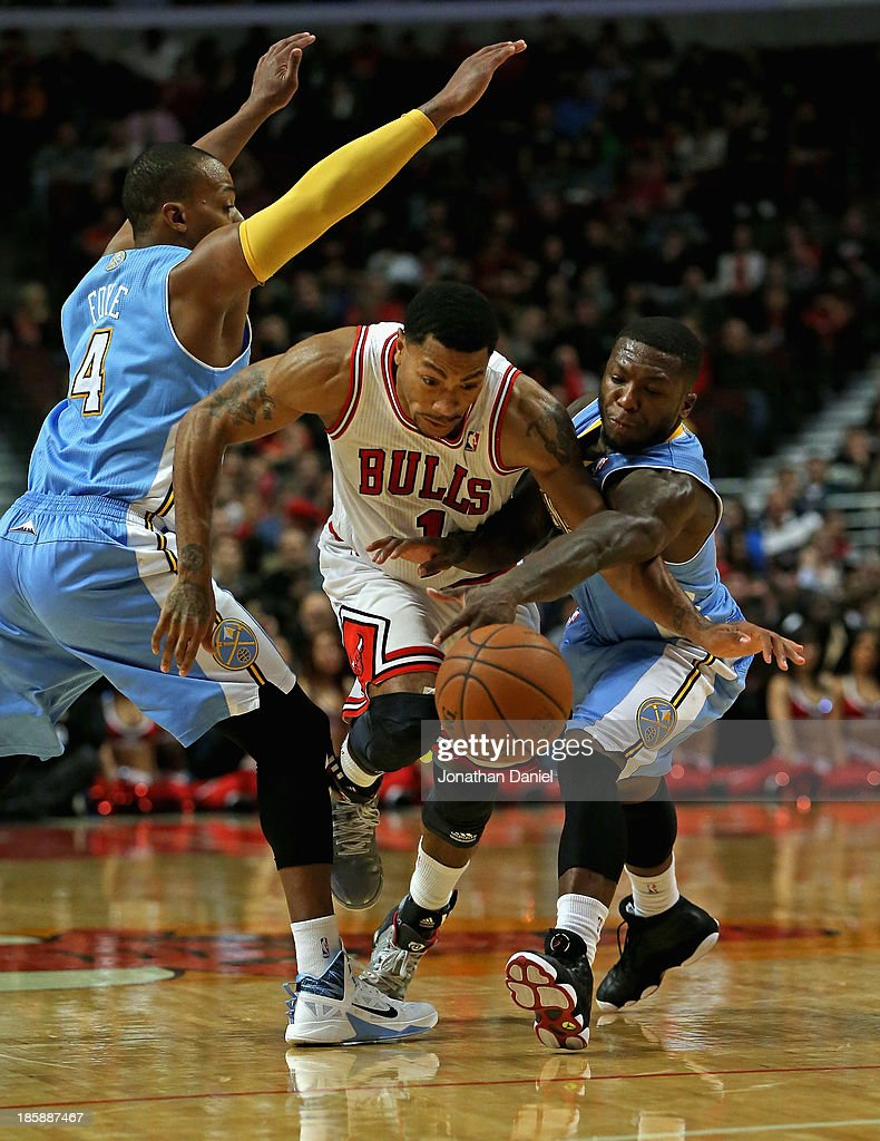 <a gi-track='captionPersonalityLinkClicked' href=/galleries/search?phrase=Derrick+Rose&family=editorial&specificpeople=4212732 ng-click='$event.stopPropagation()'>Derrick Rose</a> #1 of the Chicago Bulls is fouled by <a gi-track='captionPersonalityLinkClicked' href=/galleries/search?phrase=Nate+Robinson&family=editorial&specificpeople=208906 ng-click='$event.stopPropagation()'>Nate Robinson</a> #10 of the Denver Nuggets as he drives between Robinson and <a gi-track='captionPersonalityLinkClicked' href=/galleries/search?phrase=Randy+Foye&family=editorial&specificpeople=240185 ng-click='$event.stopPropagation()'>Randy Foye</a> #4 during a preseason game at the United Center on October 25, 2013 in Chicago, Illinois. The Bulls defeated the Nuggets 94-89.