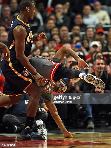 Derrick Rose of the Chicago Bulls lands akwardly as he is guard by Lavoy Allen of the Indiana Pacers at the United Center on November 16 2015 in...
