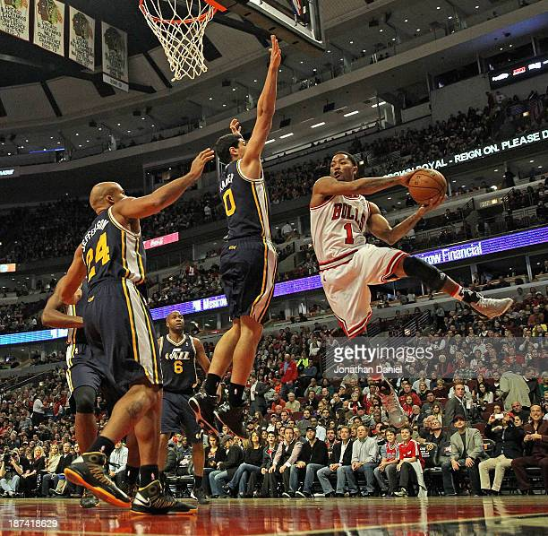 Derrick Rose of the Chicago Bulls leaps to pass against Enes Kanter and Richard Jefferson of the Utah Jazz at the United Center on November 8 2013 in...