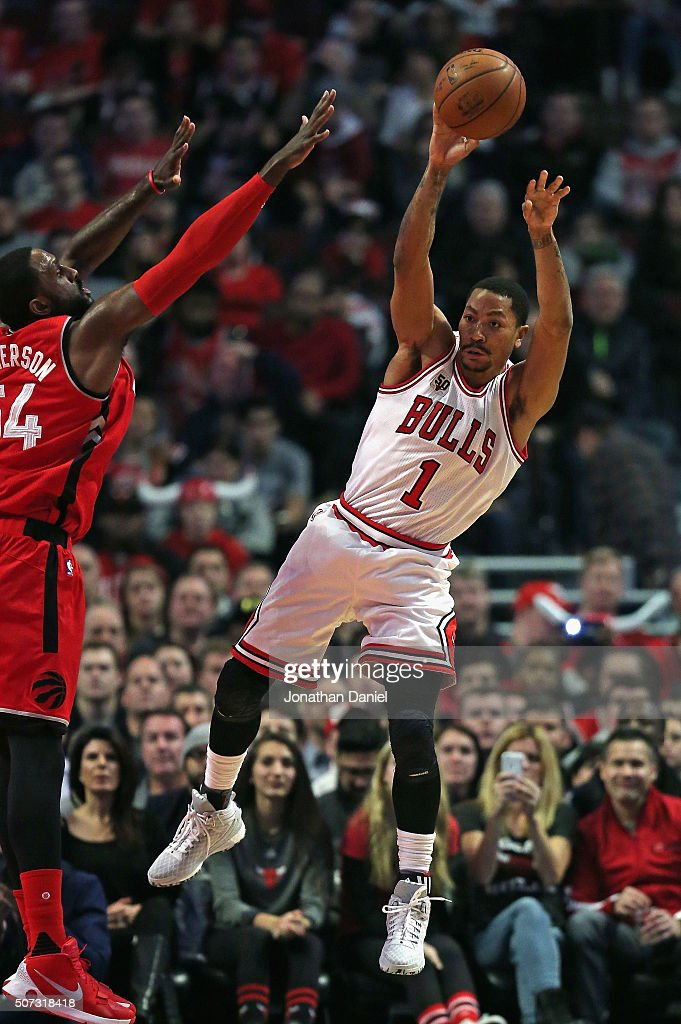 Derrick Rose #1 of the Chicago Bulls leaps to pass against Patrick Patterson #54 of the Toronto Raptors at the United Center on December 28, 2015 in Chicago, Illinois. The Bulls defeated the Raptors 104-97.